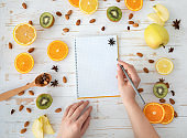 Female hand write in empty notebook on healthy food background, top view, flat lay, copy space