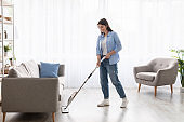 Portrait of smiling woman cleaning floor with spray mop