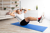 Home workout concept. Strong mature man doing abs exercises on yoga mat indoors at home