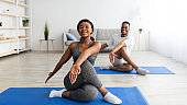 Flexibility exercises for healthier living. Athletic black couple doing yoga twist pose on home workout, copy space
