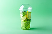 Fresh cool detox drink with cucumber, lemon and basil in plastic cup on green background. Tasty infused water to go. Proper nutrition and healthy eating. Fitness diet. Copy space for text, for menu.