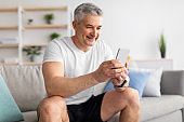 Active senior man taking break, checking smartphone or watching sports videos online, sitting on sofa after home workout