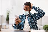 Black Man Reading Coronavirus News Via Phone Wearing Mask Indoor