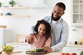 Cheerful african father teaching daughter how to cut veggies