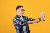 Shocked man looking at textbook in terror, screaming in despair, having problem studying for test on orange background