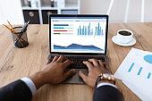 Cropped of black businessman analysing market online on laptop
