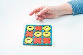 Hands elderly woman seniors play tic-tac-toe wood board game. Developmental game. Concept of family pastime. XO XO symbols.