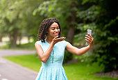 Happy black girl talking to her boyfriend online, sending air kiss on mobile phone at park