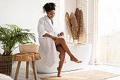 Black Lady Shaving Legs Using Razor Sitting In Bathroom Indoors