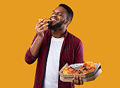 African Young Man Enjoying Pizza Posing With Box, Yellow Background