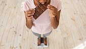Diet breakdown and unhealthy nutrition. Above view of African American woman eating chocolate bar on scales, closeup