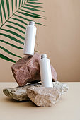 Natural beauty cosmetic bottles white mockup cosmetic product for skincare on stone pedestal beige background with palm leaves. Natural skin body care lotion bottles levitation white cosmetic bottles.