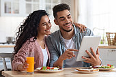 Loving Arab Couple Eating Breakfast Together And Using Digital Tablet In Kitchen