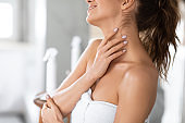 Woman Touching Neck Moisturizing Skin After Shower Standing In Bathroom