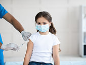 Little girl in mask getting covid-19 vaccine shot at clinic. Population protection and infectious disease prevention