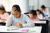 Portrait of boy sitting at desk in classroom and writing