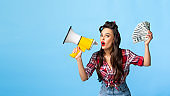 Sexy pin up lady with money screaming into megaphone on blue studio background, banner design with empty space