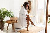 African American Woman In Bathrobe Touching Smooth Legs In Bathroom