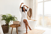 Relaxed African American Woman Stretching Arms Enjoying Morning In Bathroom