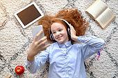 Girl wearing headphones enjoying music with smartphone