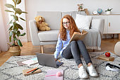 Girl sitting on the floor, reading book, using laptop