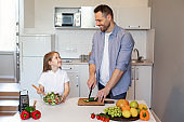 Happy Dad And Little Daughter Cooking Making Salad In Kitchen