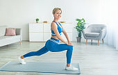 Woman doing forward lunges looking at camera