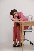 Stressed businesswoman staring at pink slip