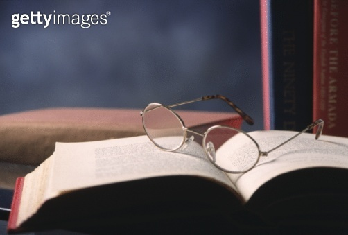 Still life of spectacles on open book in study