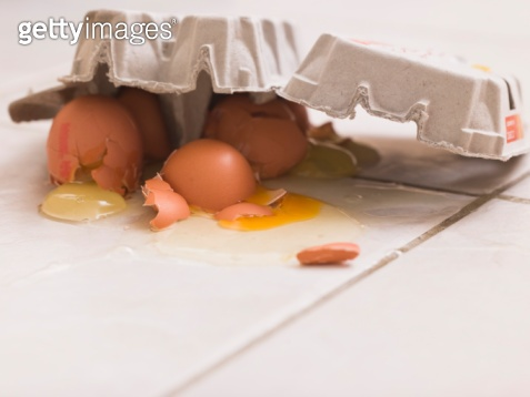 Smashed carton of eggs on floor