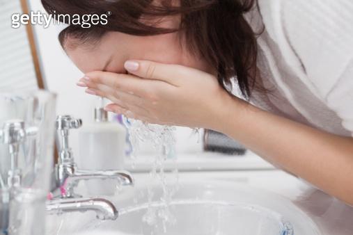 Close-up of woman washing face