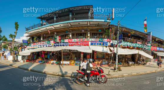 Young men riding motorbike outside colourful stores Pokhara Nepal