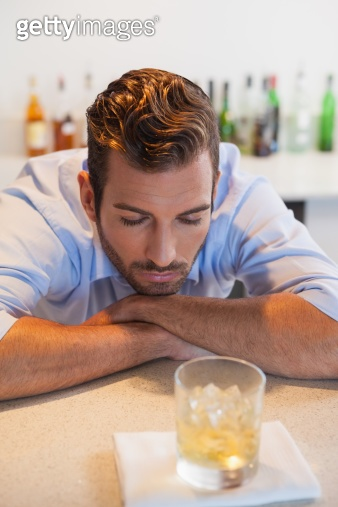 Drunk businessman looking at his whiskey glass