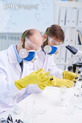 Scientists with gloves working with chemicals