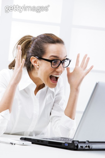 Victory - Young business woman using a laptop at work