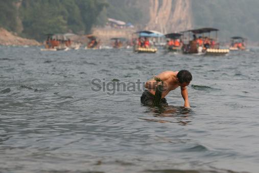 Worker cleaning kelp off Lijiang River