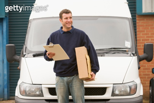 Delivery person standing with van holding clipboard and box smil