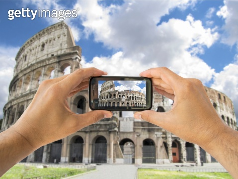 tourist holds up camera mobile at coliseum in Rome