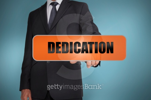 Businessman touching the word dedication