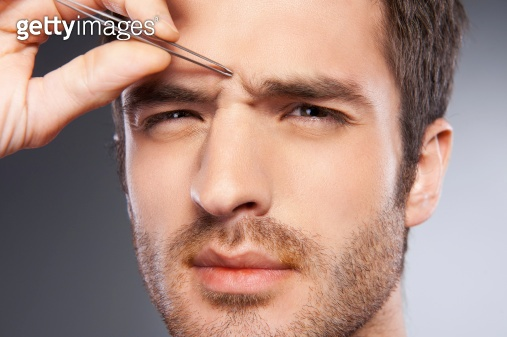 Man tweezing eyebrows.