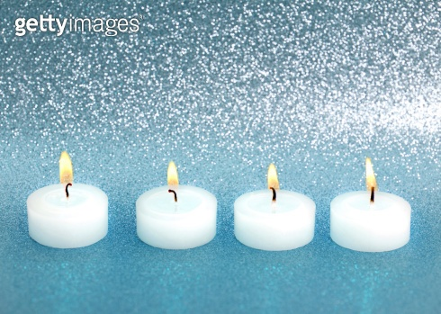 burning candles over silver blue shiny background