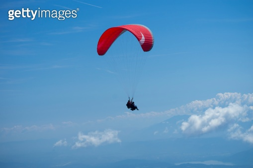 Paraglider is flying over Austrian Alps