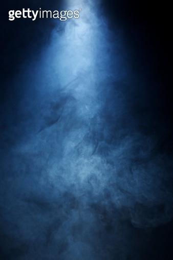Beam of Light Passing Through Blue Smoke onBlack Background
