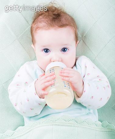 Beautiful little baby with milk bottle under warm knitted blanket