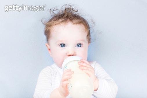 Sweet baby in a blue sweater drinking milk