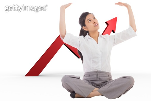 Composite image of businesswoman sitting cross legged pushing up