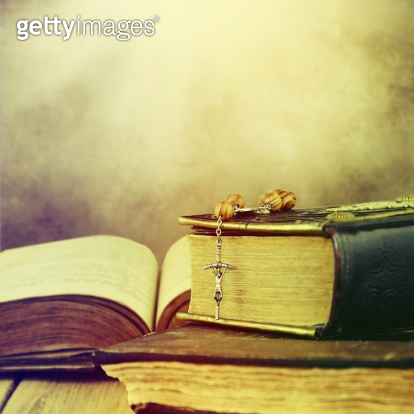 Christian cross necklace next to holy Bible.