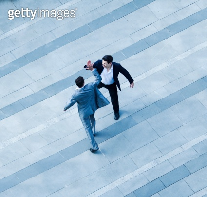Aerial view of businessmen giving each other high-five on sidewalk