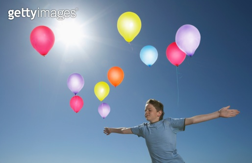 Carefree Boy In Midair With Colorful Balloons