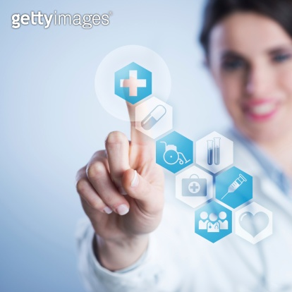 Young female doctor using touch screen interface.